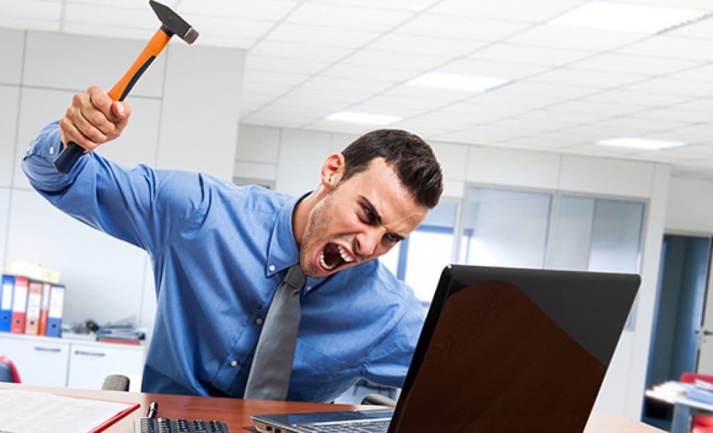 Angry man smashing his laptop